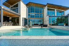 """Located on Benthaven Island in Montgomery, this architectural gem offers sweeping views of Lake Conroe from nearly every room and just hit the market at $4.25 million. Known as the """"Glass House,"""" the modern mansion boasts four bedrooms, four full and one half bathrooms, interior private courtyard, two-story glass wine room, private apartment, infinity pool and sundeck, dock and is available fully furnished."""