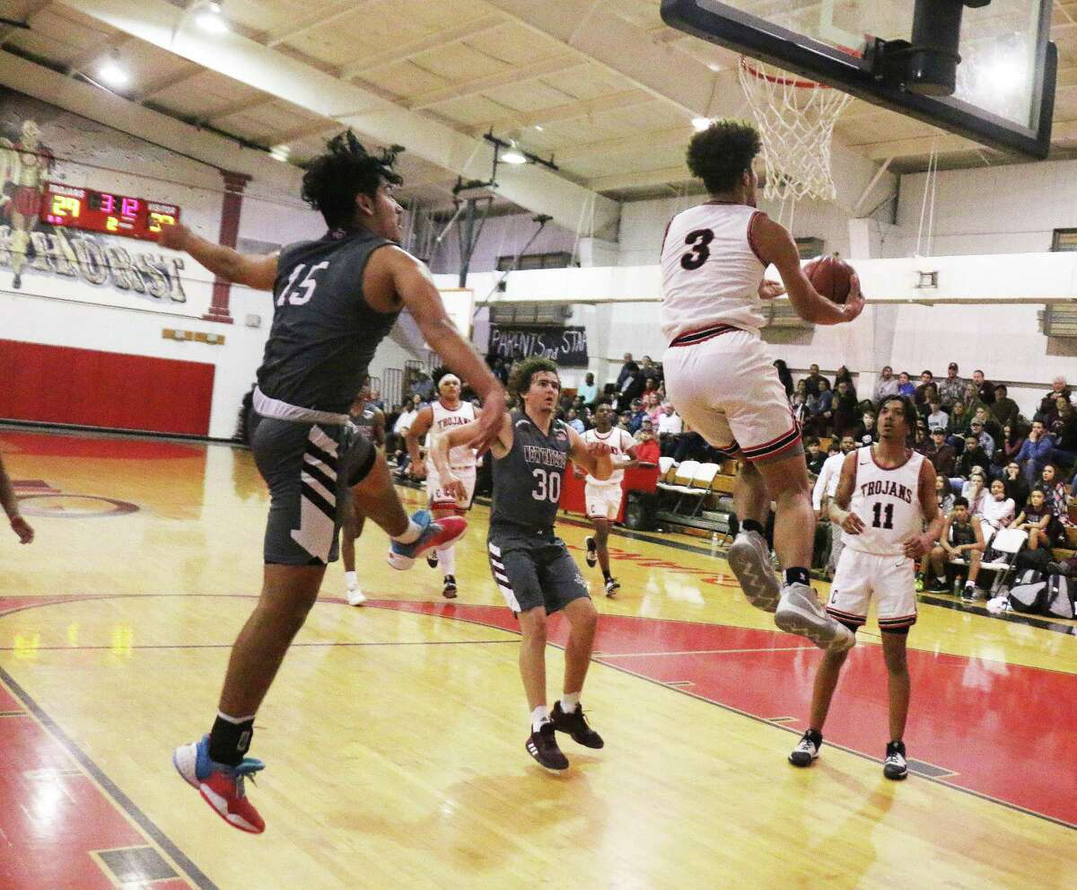 Coldspring's Jacoby Bishop goes skyward for a reverse shot from under the basket while New Waverly sophomore Sebastine Amaro, who was guarding him, watches the phenom score. The Trojans outlasted New Waverly, 80-75, in a battle for district supremacy.
