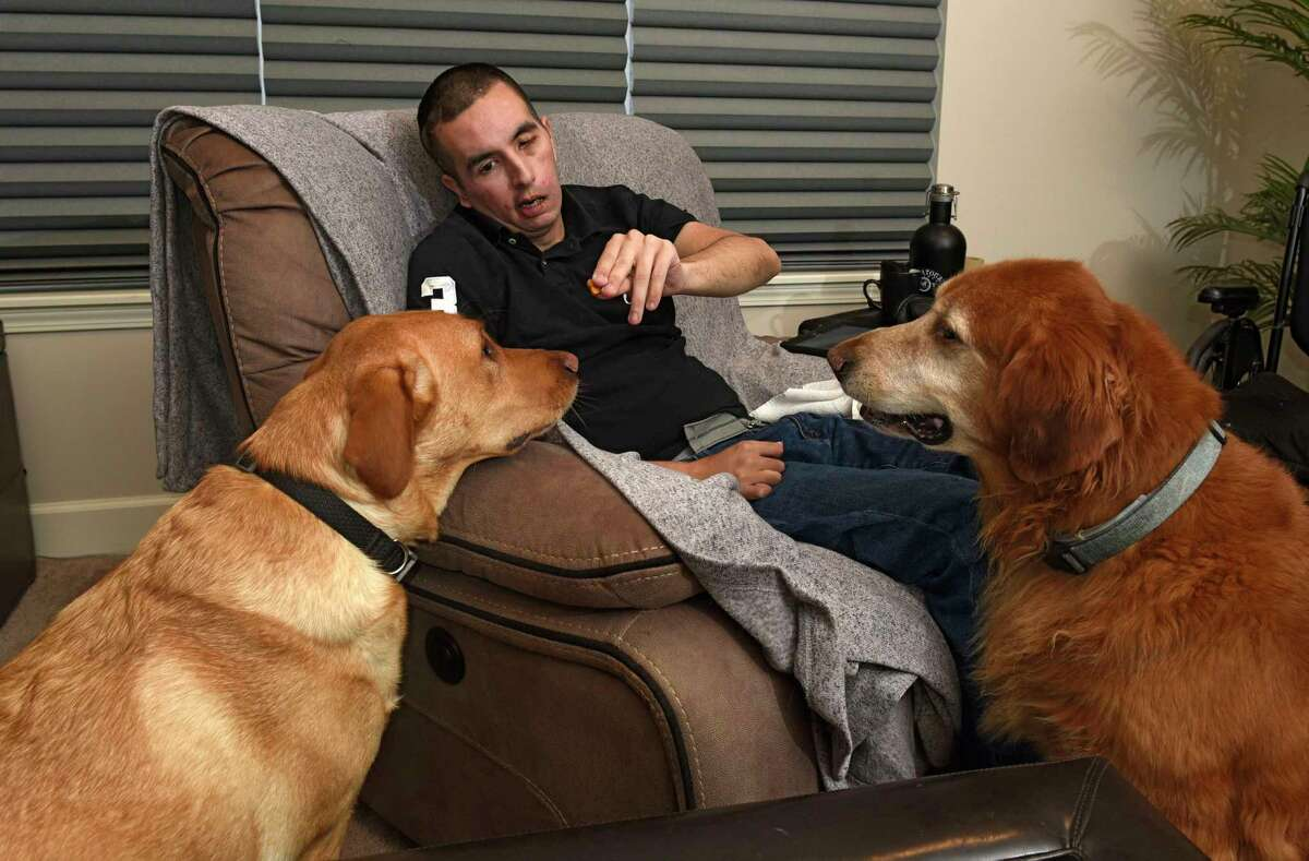 John Shelffo feeds his dogs Leo and Pogo treats at home on Wednesday, Jan. 22, 2020 in Malta,  N.Y. John suffered a massive brain tumor and stroke 10 years ago that left him in need of home health aides. (Lori Van Buren/Times Union)
