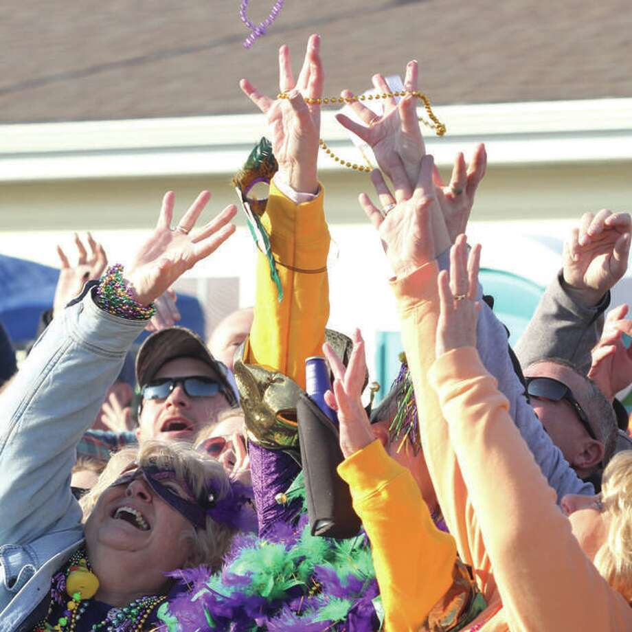 "A group of spectators grab for beads thrown into the crowd during a previous Wordi Gras, a parade held annually in Worden. Organizers tout the event, now 10 years old, as a ""redneck Mardi Gras."" Photo: Scott Cousins