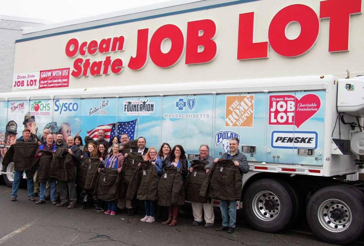 Associates from Ocean State Job Lot's Wareham, Buzzards Bay, Middleboro and Plymouth locations display some of the winter coats that are being distributed regionally to help local veterans in need stay warm this winter. Nearly 30,000 coats will be donated this season thanks to the generosity of Ocean State Job Lot customers. Many of the coats will be delivered via the 'Mobile Empowerment Center' (background), a first-of its-kind canteen designed to provide perishable and nonperishable food, diapers and health and wellness products to veterans and active-duty military and their families.