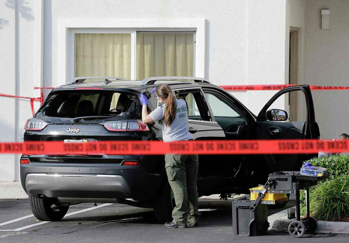 A forensic technician works on the vehicle authorities say officers fired shots at, that breached security at President Donald Trump's Mar-a-Lago resort in Palm Beach, Friday, Jan. 31, 2020, in West Palm Beach, Fla.