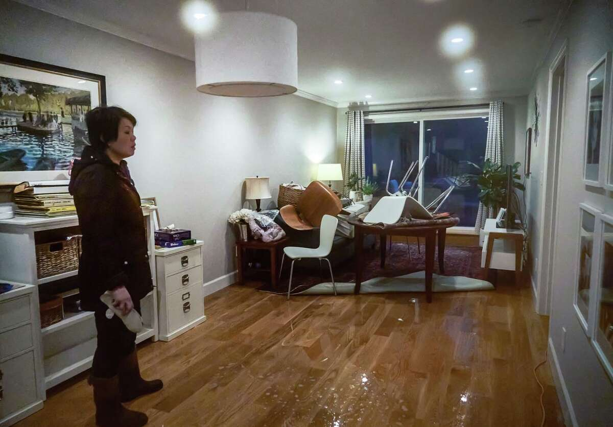A homeowner who didn't want to be identified stands in her living room after heavy rains caused flooding into homes at 15th Street and Wawona Avenue in San Francisco in December.