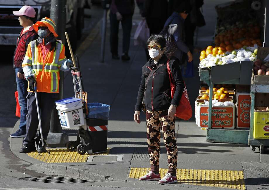 A masked worker and shopper wait for a street signal Friday, Jan. 31, 2020, in the Chinatown district in San Francisco. As China grapples with the growing coronavirus outbreak, Chinese people in California are encountering a cultural disconnect as they brace for a possible spread of the virus in their adopted homeland. Photo: Ben Margot / Associated Press