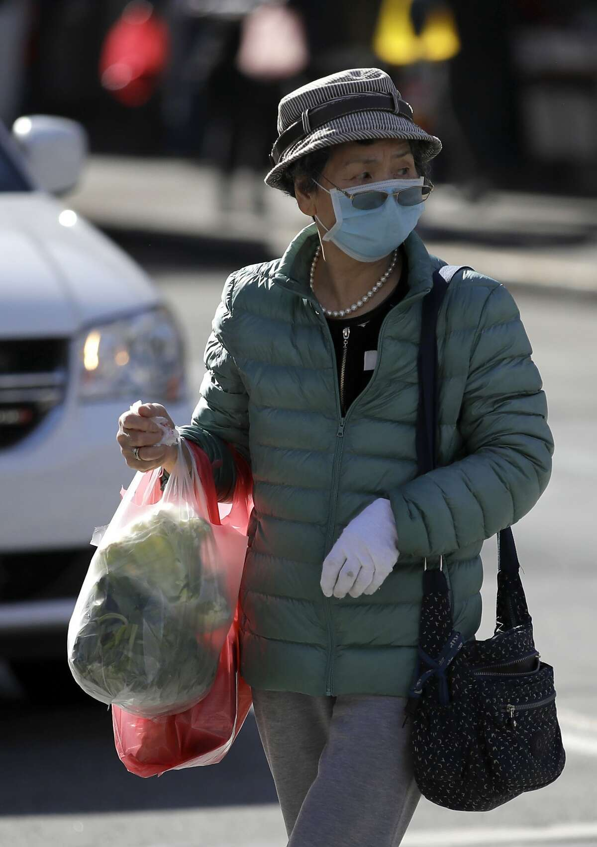 A masked shopper walks across a street Friday, Jan. 31, 2020, in the Chinatown district of San Francisco. As China grapples with the growing coronavirus outbreak, Chinese people in California are encountering a cultural disconnect as they brace for a possible spread of the virus in their adopted homeland. (AP Photo/Ben Margot)
