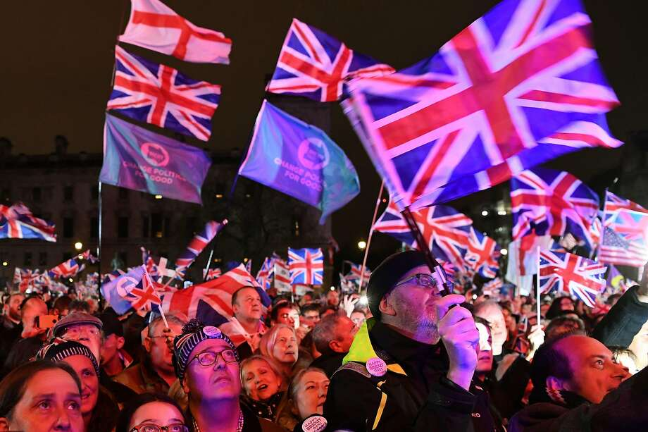 Brexit supporters wave Union Jack flags in London's Parliament Square as they celebrate Britain's official separation from the European Union. Photo: Daniel Leal-Olivas / AFP Via Getty Images