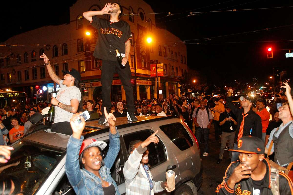 Giants fans on Valencia St. celebrate their team's victory in the 2014 World Series on Wednesday, Oct. 29, 2014.