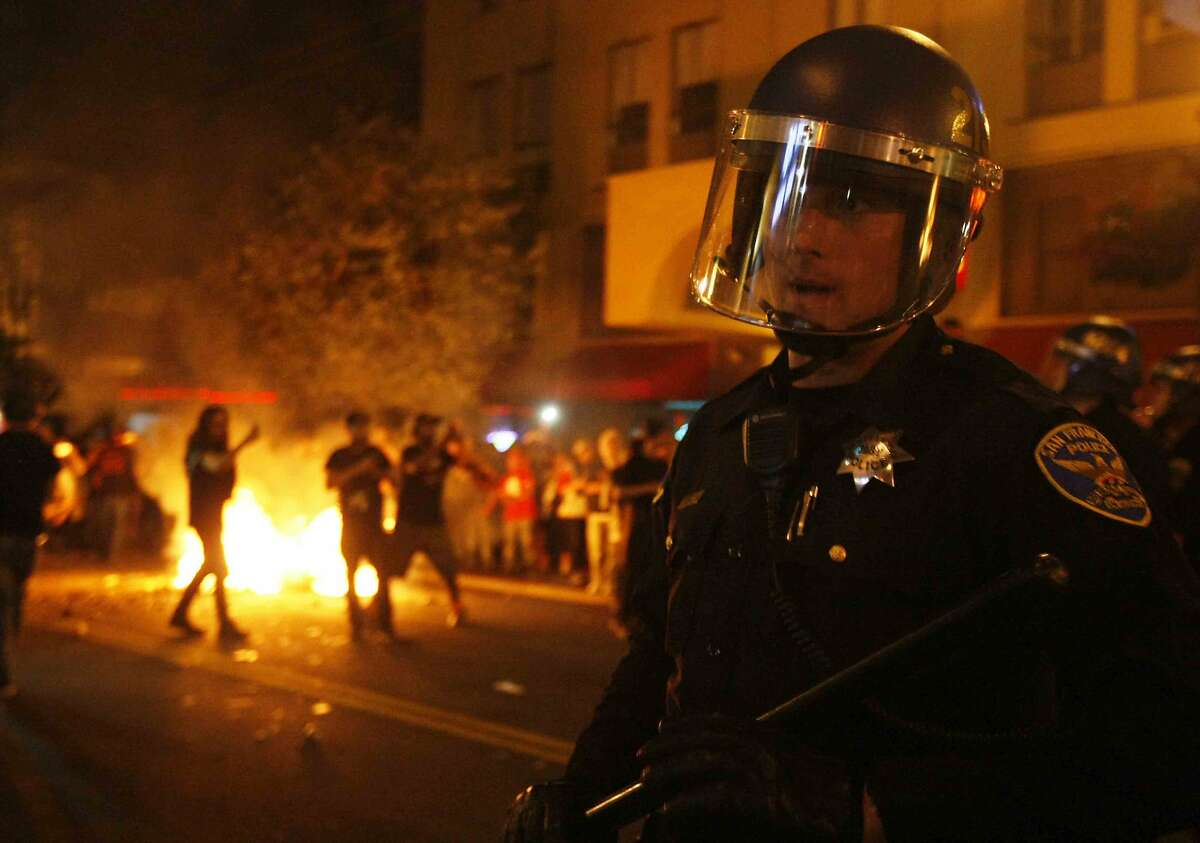 A riot police officer tries to tame the scene after Giants fans riot in the streets at 22nd and Mission after the San Francisco Giants win the World Series against the Kansas City Royals Wednesday, October 29, 2014.