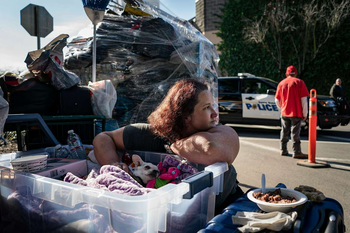 Sandra Morton, 39, a cook at Denny's, sits outside with her dog and her belongings she moved out of her home on the Joe Rodota Trail in Santa Rosa, California on January 31st, 2020.