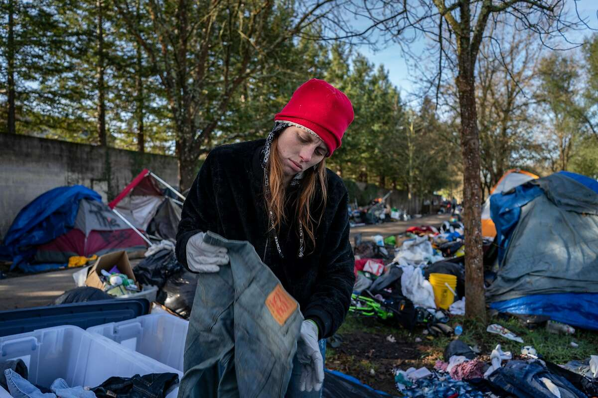Merry Potter, 28, organizes her belongings by separating clothing she wants to keep and throw out where she's been living on the Joe Rodota Trail before moving into her new shelter in Santa Rosa, California on January 31st, 2020.