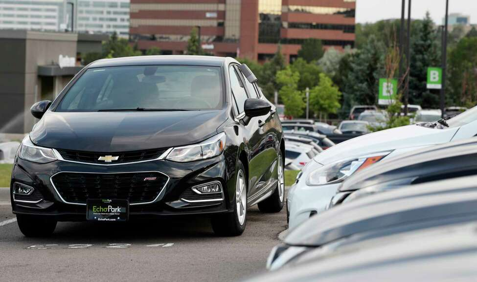 FILE - In this June 26, 2018, file photograph, a used 2017 Chevrolet Cruze sits in a row of other used, late-model sedans at a dealership in Centennial, Colo. Consumers bought an estimated 40.4 million used vehicles last year, likely passing the old record of 40.2 million set in 2018, according to figures from the Edmunds.com auto pricing site. (AP Photo/David Zalubowski, File)