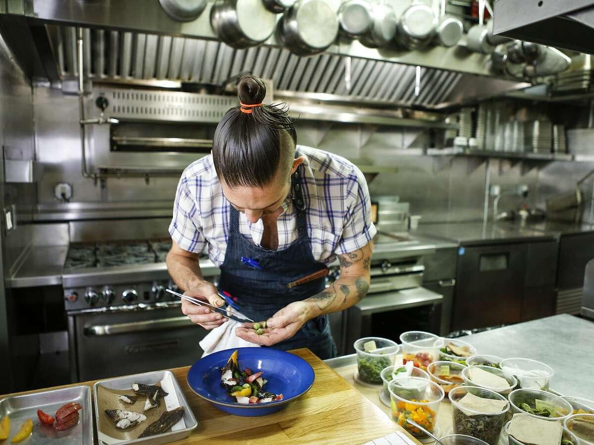 Al's Place chef/owner Aaron London plates a dish of Stone Fruit Curry, Black Lime-cod, Green Bean and Blueberry on Monday, Aug. 17, 2015 in San Francisco, Calif.