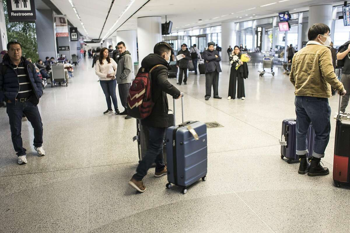 Yibo Zhu, center, leaves SFO after flying from China on Thursday, January 30, 2020 in San Francisco, Calif. Airlines are cancelling some flights to China because of concerns over the coronavirus.