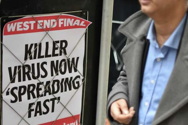 "People walk past a news banner that reads ""Killer virus now spreading fast"" at London's Bank station on Jan. 31, the same day the US declared the coronavirus a public health emergency."