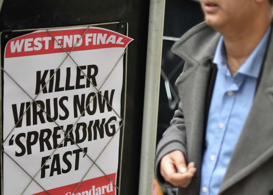 """People walk past a news banner that reads """"Killer virus now spreading fast"""" at London's Bank station on Jan. 31, the same day the US declared the coronavirus a public health emergency. Photo: CBSI/CNET"""