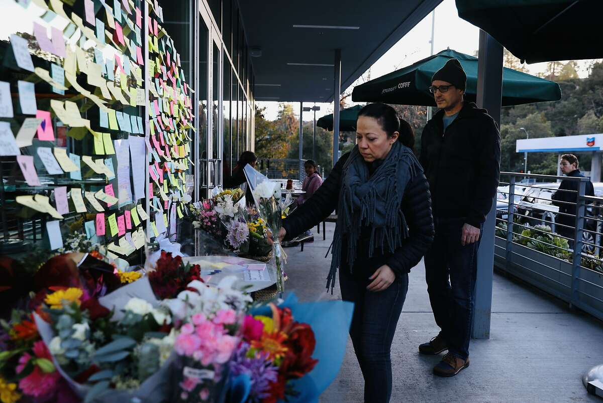 Nabeela Ali-Hasan, left, and Chris Rowe, both of Montclair, place a bouquet of flowers at Starbucks, located at 2080 Mountain Blvd., in Montclair, Calif., on Wednesday, January 2, 2020. Two days prior, on New Year's Eve, a man was critically injured outside the coffee shop after he chased the thief who stole his laptop. The man later died of his injuries as a result of the incident. The Oakland Police Department announced on New Year's Day that two men had been arrested in connection with Tuesday's episode.