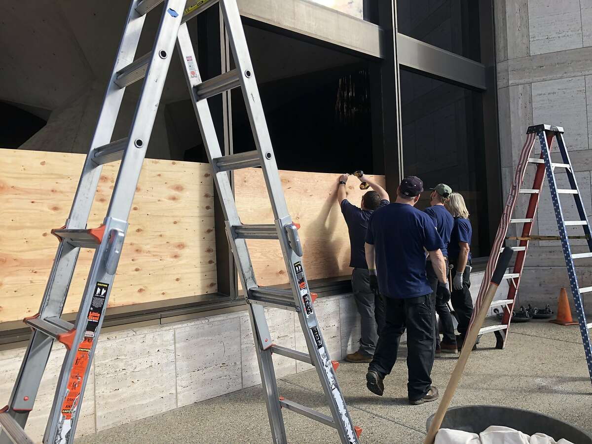 Workers boarding up windows at St. Mary's Cathedral in San Francisco after a vandal broke nine windows early Friday morning on Jan. 31, 2020.