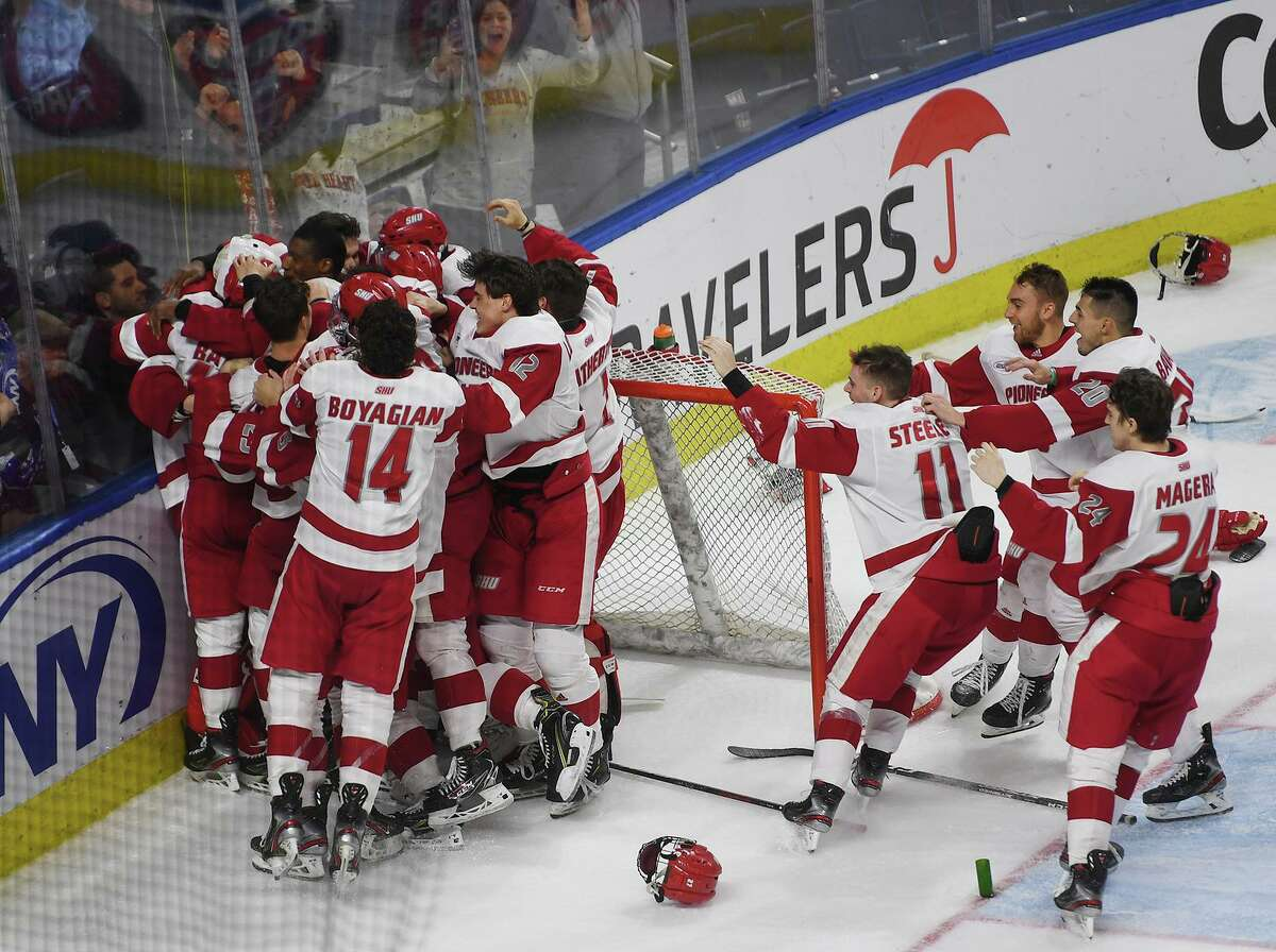 Sacred Heart teammates mob goalie Josh Benson following their team's 4-1 victory over Quinnipiac in the championship game of the Connecticut Ice college hockey tournament at the Webster Bank Arena last season in Bridgeport.