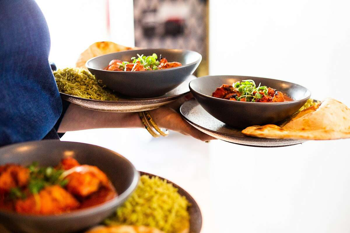 Jaclyn Davis serves three tandoori chicken bowls to lunch customers at August 1 Five on January 31, 2020.