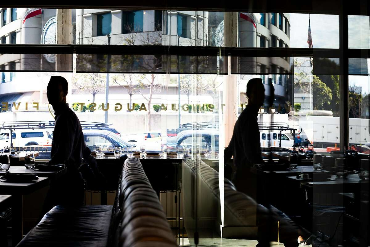 Manager of August 1 Five, Jordan White, helps buss a table during the lunch rush on January 31, 2020 in downtown San Francisco.