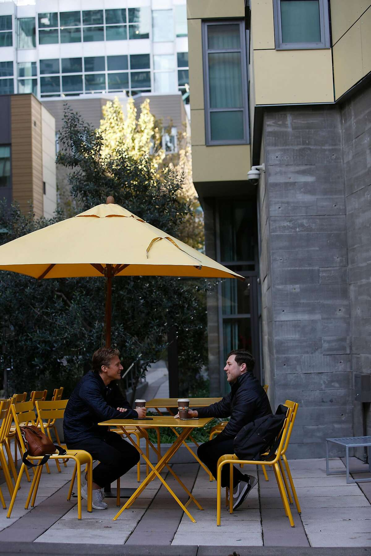 Emmett Mountjoy (l to r) and Travis Salle, both of San Francisco talk at a table while enjoying a beverage outside Philz Coffee along Folsom Street on Friday, January 17, 2020 in San Francisco, Calif.