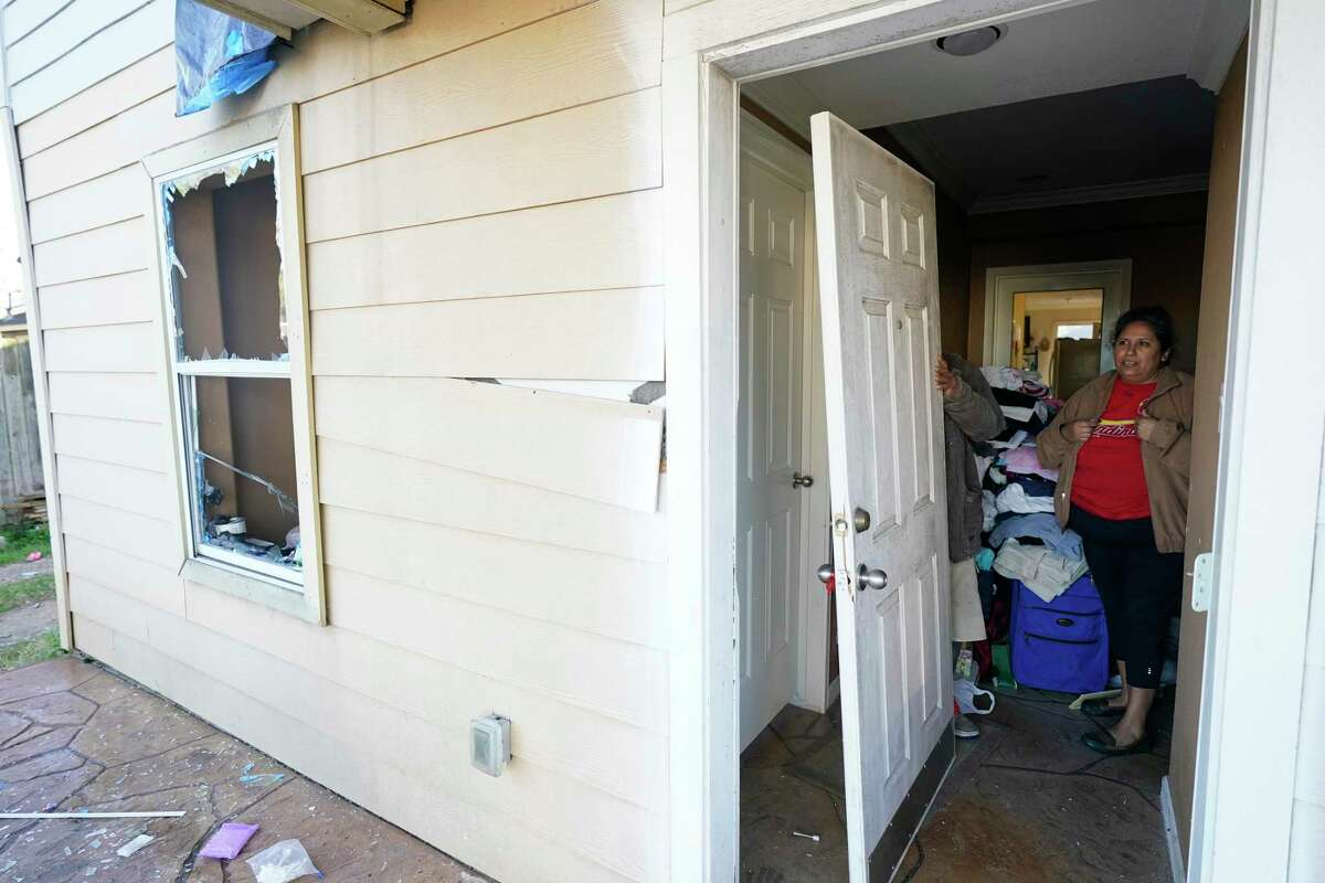 Maria Diosdado waits as her husband, Eduardo Flores, moves the back door that was blown off its hinges at their home on Talina Way just one street east of Watson Grinding and Manufacturing, located at 4525 Gessner Rd., where an explosion occurred Friday, Jan. 24, 2020, in Houston.