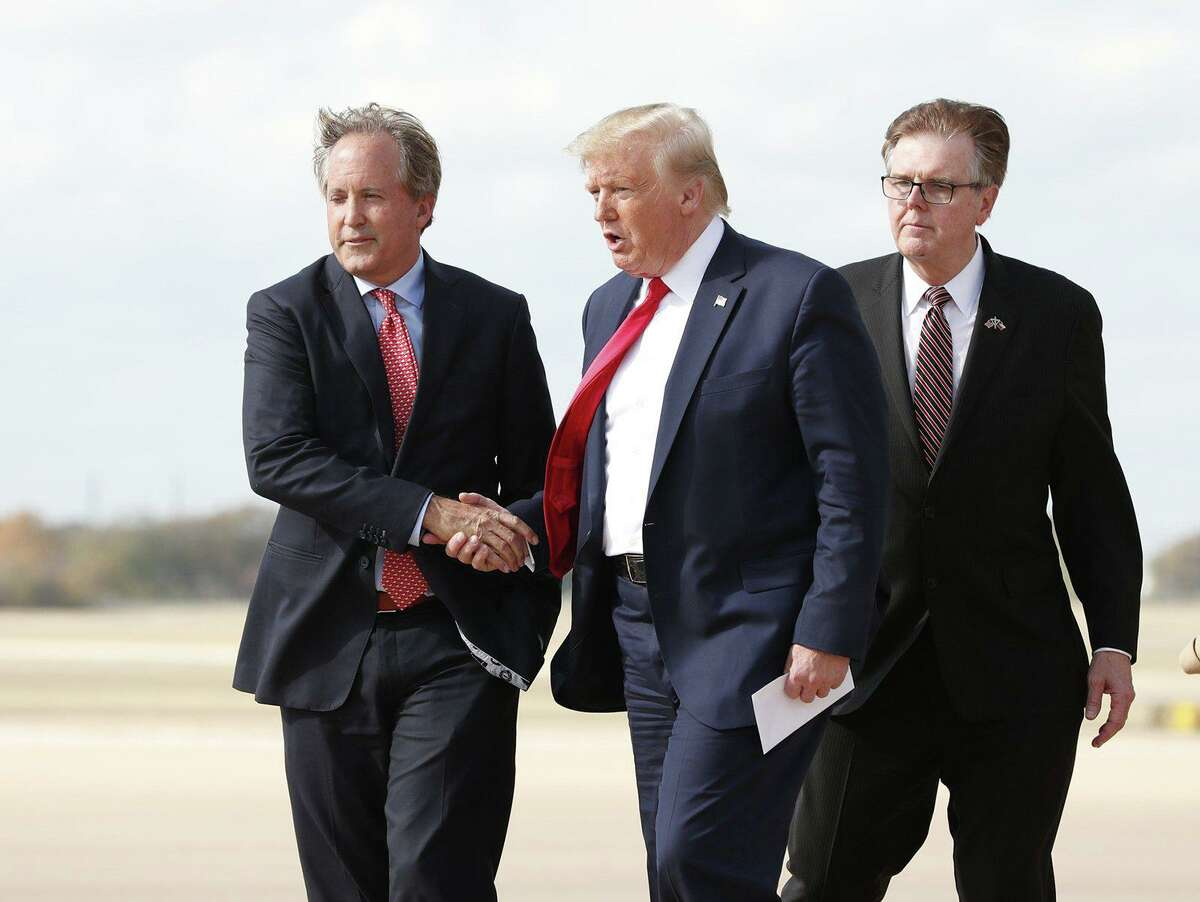 President Donald Trump greets Texas Attorney General Ken Paxton as Lt. Governor Dan Patrick follows at Austin Bergstrom International Airport Wednesday November 20, 2019 before his visit to the Apple campus.