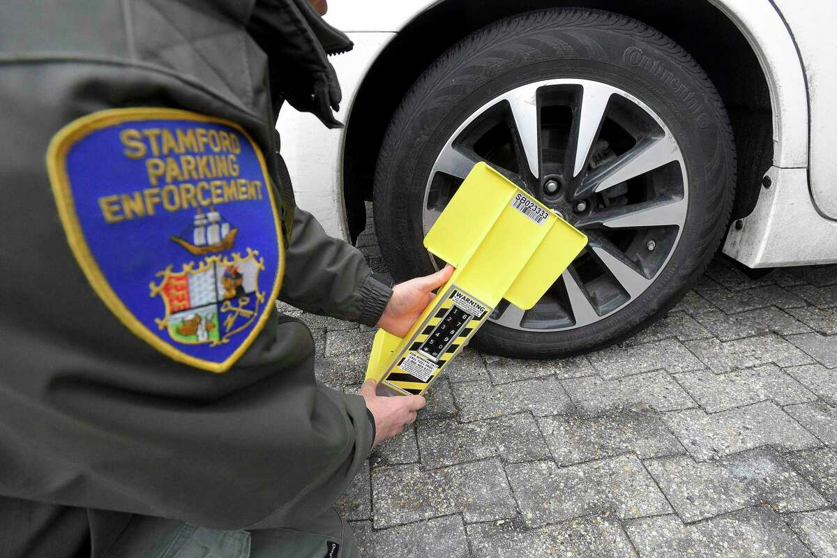 A Stamford Parking Enforcement Officer demonstrates use of a self-releasing electronic boot last year.