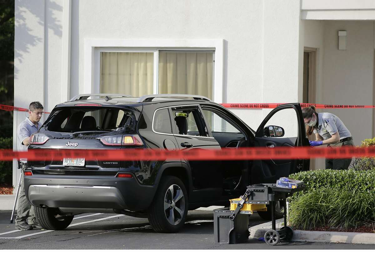 Forensic technicians work on the vehicle authorities say officers fired shots at, that breached security at President Donald Trump's Mar-a-Lago resort in Palm Beach, Friday, Jan. 31, 2020, in West Palm Beach, Fla. (AP Photo/Terry Renna)