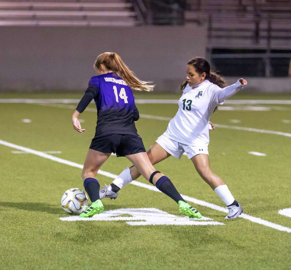 Montgomery forward Jenna Attebery (14) and Huntsville midfielder Eva Zamudio (13) fight for control of the ball in a District 20-5A match in Montgomery, Friday, Jan. 31, 2020.