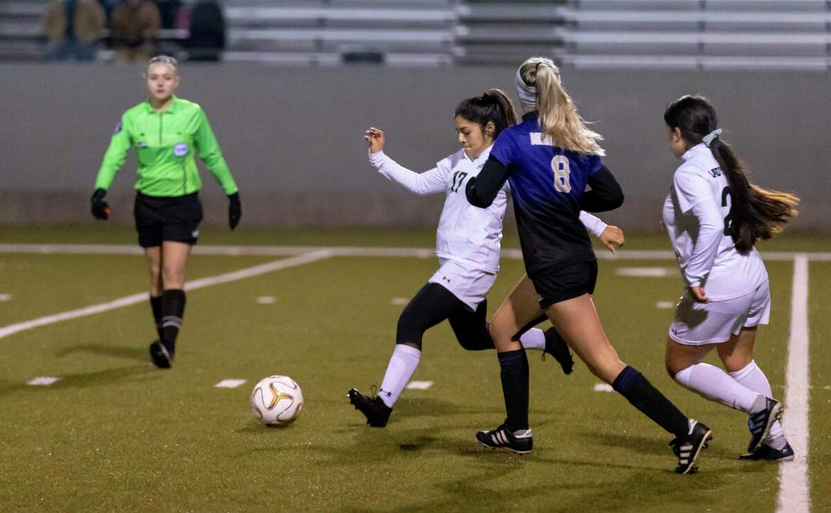 Huntsville forward Arianna Solis (17) attempts to pass the ball under pressure from Montgomery midfielder Tallyn Herle (8) in a District 20-5A match in Montgomery, Friday, Jan. 31, 2020.