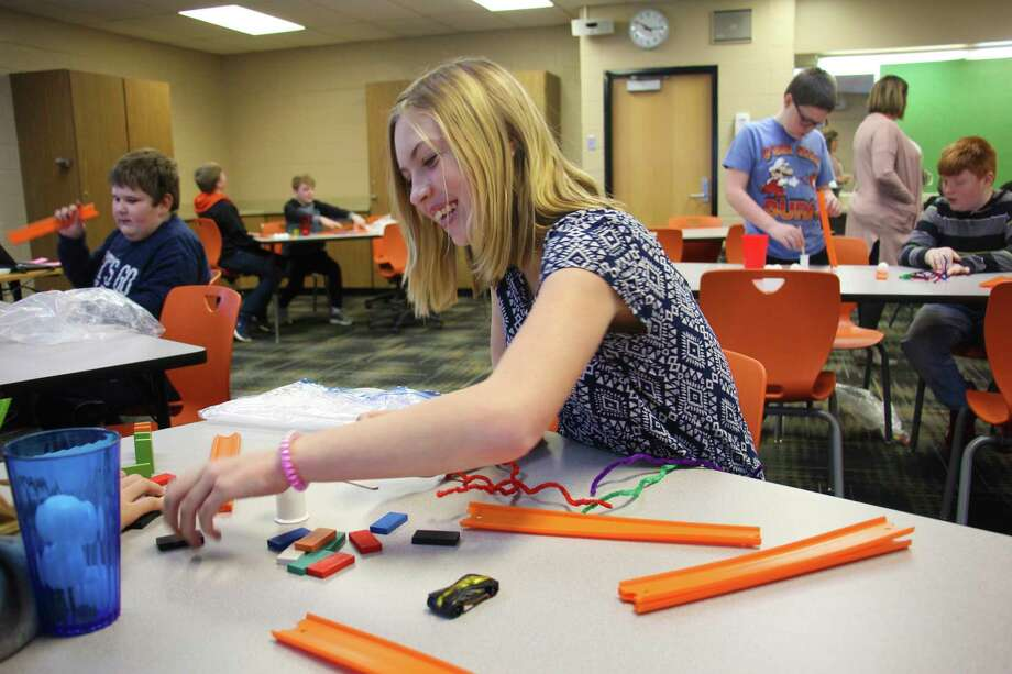 Harbor Beach student Abby Klaski works with her classmate to complete the Rube Goldberg Challenge STEM project. (Sara Eisinger/Huron Daily Tribune)