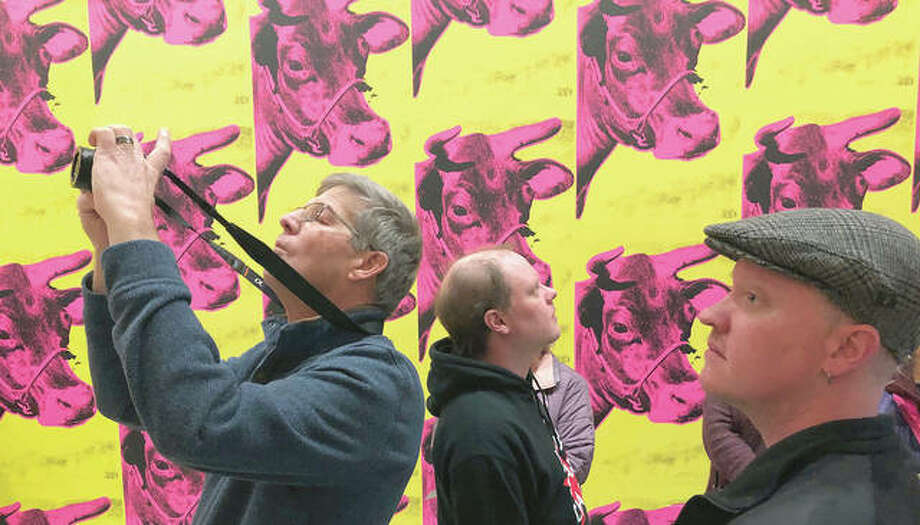 """Patrons of the Art Institute of Chicago look at an exhibit of works by Andy Warhol. The exhibit """"From A to B And Back Again"""" features a room decorated in Cow Wallpaper, the first in a series of wallpaper designs Warhol created from the 1960s to the 1980s."""