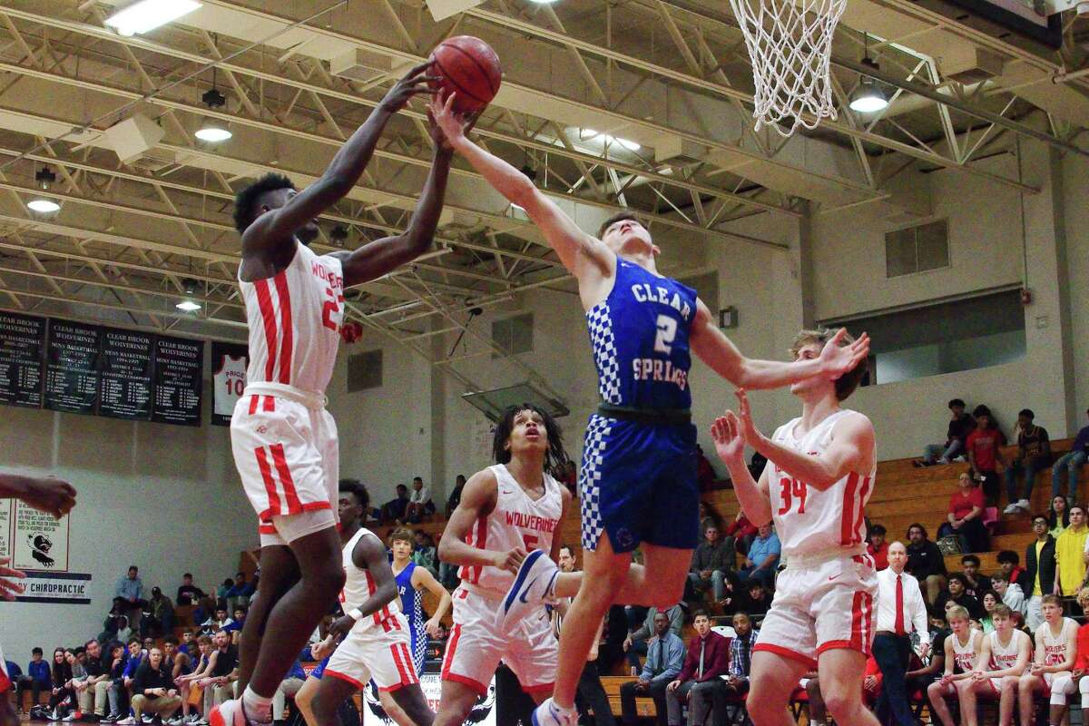 Clear Brook's Zion Little (23) and Clear Springs' Noah Van Chau (2) fight for a rebound Tuesday at Clear Brook High School. Clear Brook won the game, 50-48, on a 3-point shot at the buzzer by KeMauri Millender.