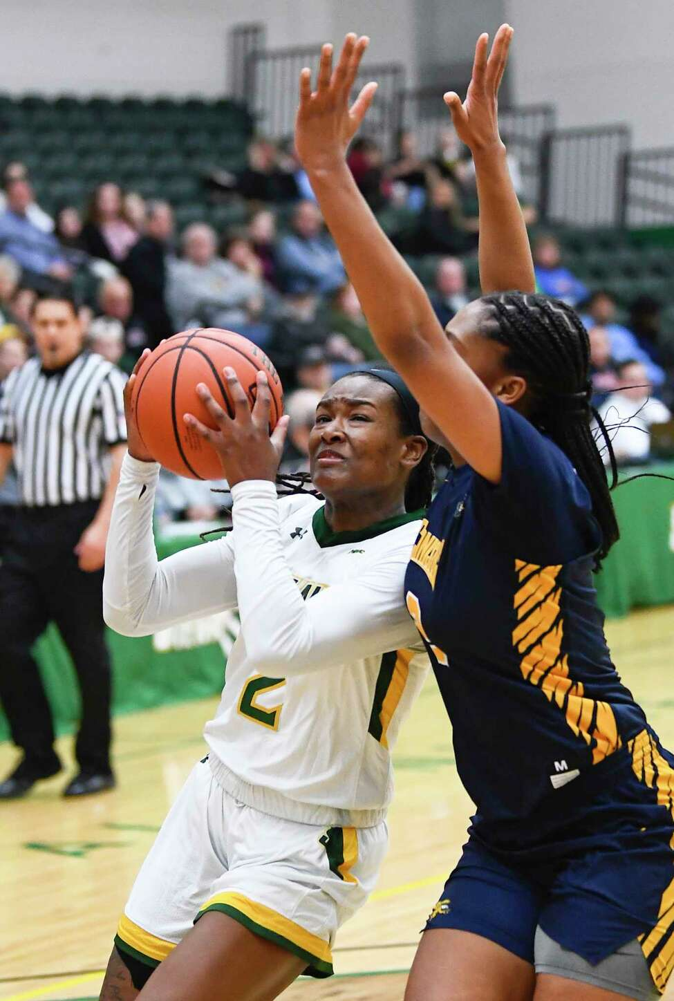 Siena guard Amari Anthony, left, scores against Canisius guard Shayla Sweeney during the first half of a NCAA women's college basketball game, Saturday, Feb. 1, 2020, in Loudonville, N.Y.