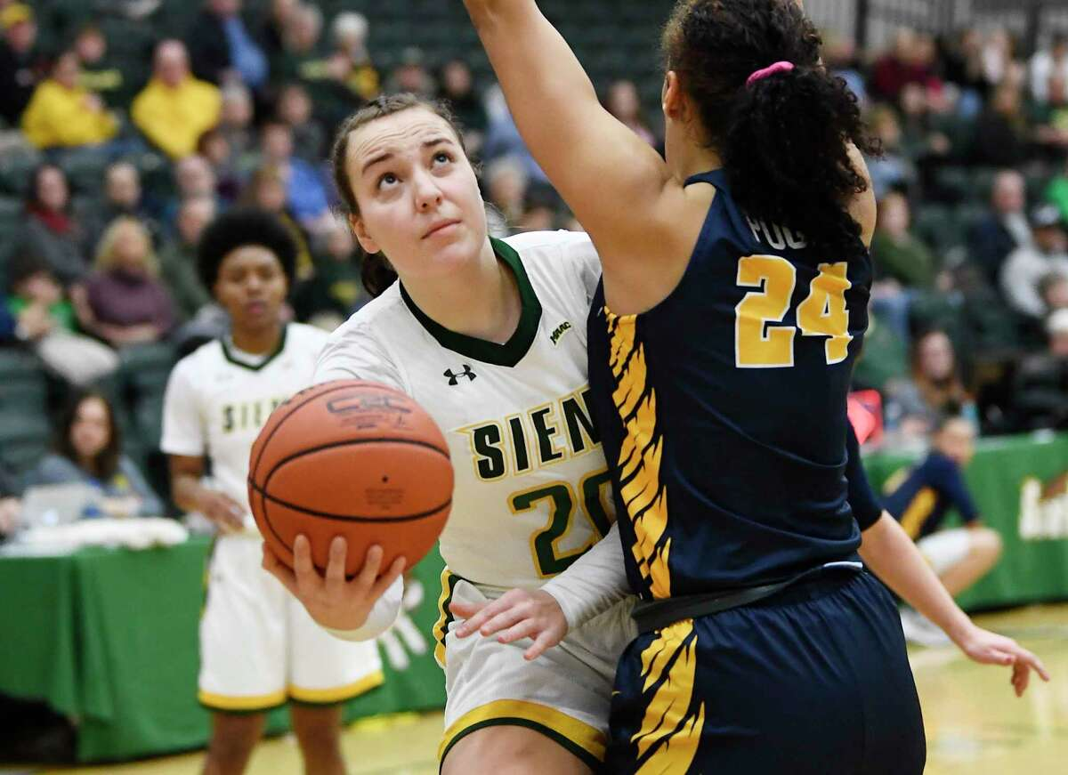 Siena guard Margo Peterson (20) scores against Canisius forward Tiana Pugh (24) during the first half of a NCAA women's college basketball game, Saturday, Feb. 1, 2020, in Loudonville, N.Y.