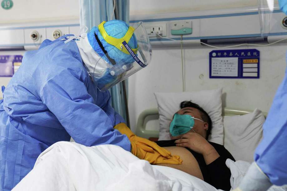 File photo: This photo taken on January 28, 2020, shows a medical staff member checking a patient infected by the novel coronavirus inside an isolation ward at a hospital in Zouping in China's easter Shandong province. Photo: Contributed Photo / Getty Images / AFP or licensors