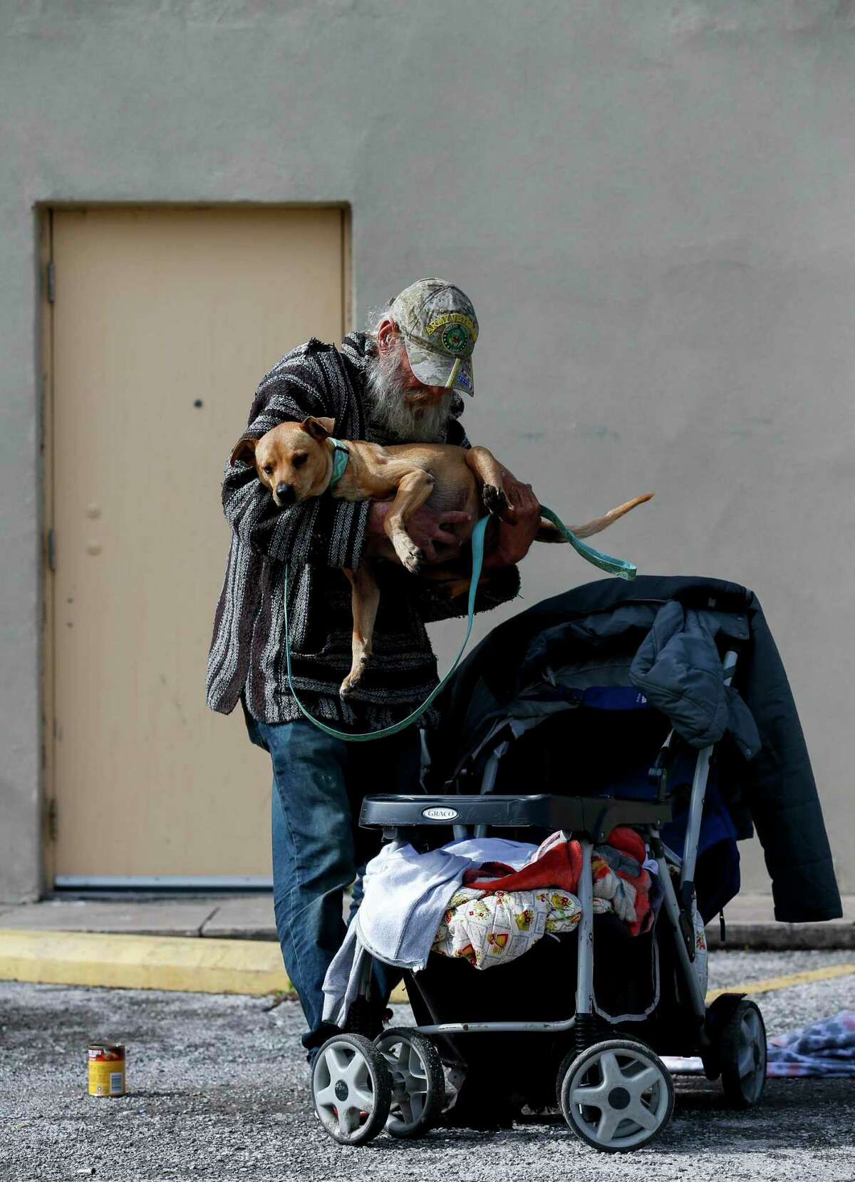 Billy Wooldridge places his dog, Kujo, in a stroller after feeding him on a Family Dollar parking lot Thursday, Jan. 23, 2020, in Galveston, Texas. Wooldridge is currently homeless in Galveston.