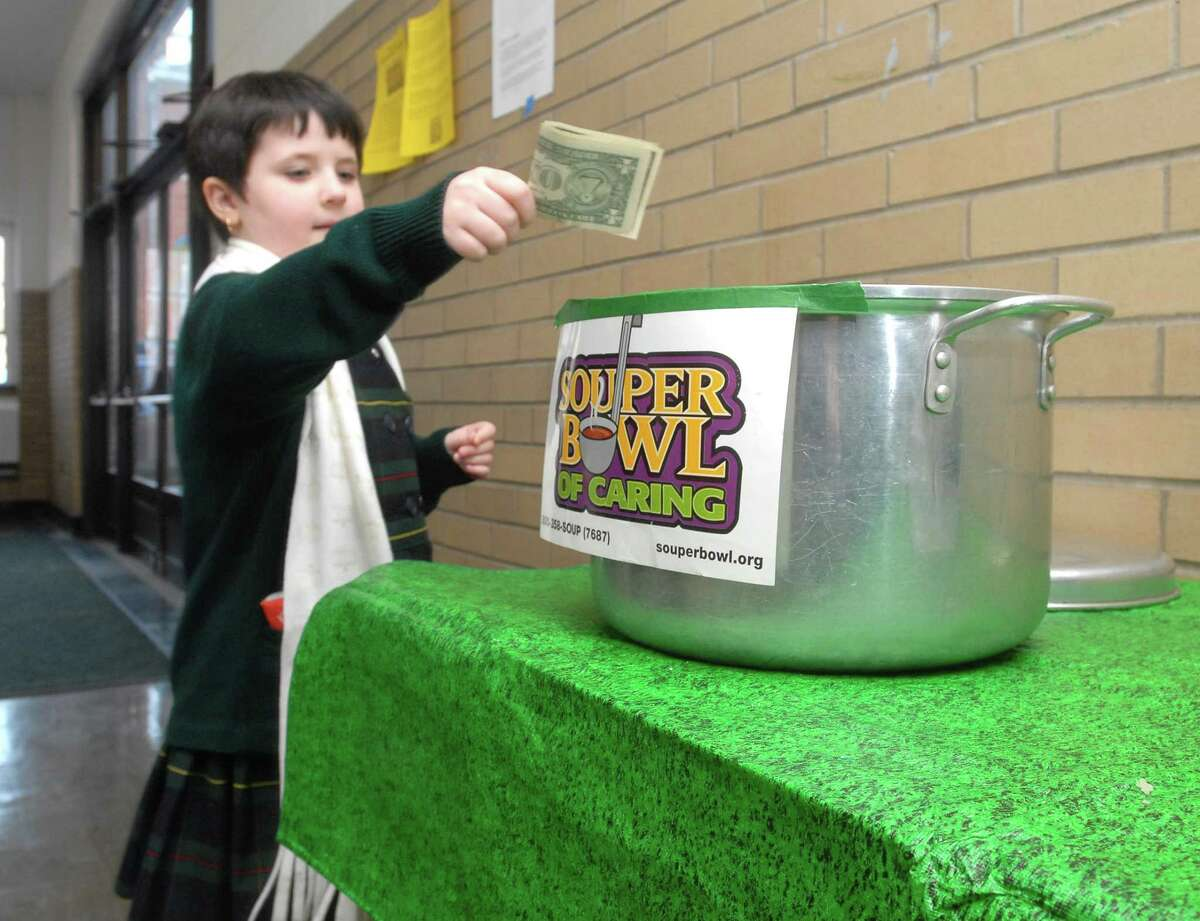 Brad Horrigan   New Haven Register. BH0280. Milford, Connecticut - 02.01.09: Amelia Mower, 6, drops a dollar bill into a stock pot of collection money at the Fourth Annual Souper Bowl of Caring at St. Ann School. Money and food are collected for Beth El-Center soup kitchen and Bridgeport Rescue Mission.