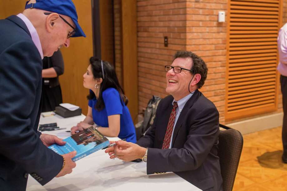 "Nicholas Kristof and Sheryl WuDunn sign copies of ""Tightrope"" at an event held in Houston, Texas, on Jan. 16. Photo: File Photo"