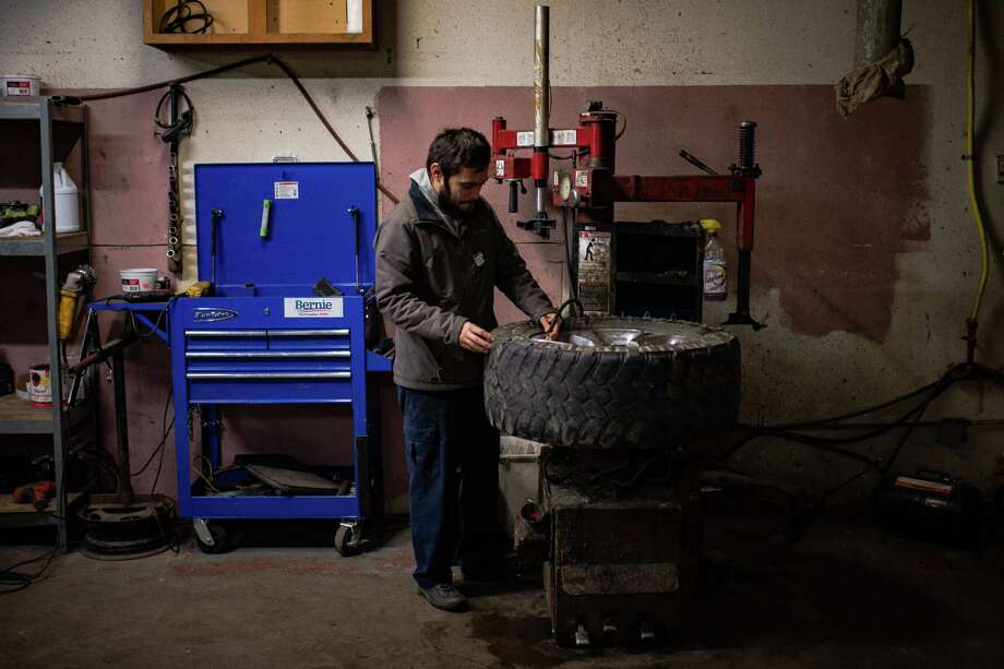 Luis Gomez, 31, a former DACA recipient who is in the process of becoming a citizen, after marrying a citizen, adds air to a tire at work on Friday in Des Moines Iowa. Photo: Washington Post Photo By Salwan Georges / The Washington Post