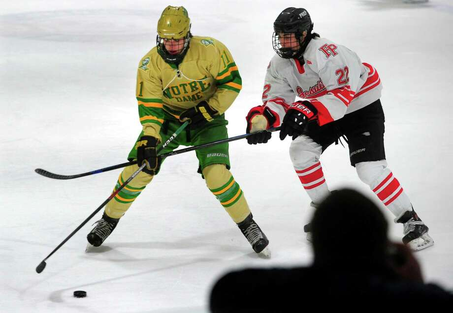 Notre Dame-West Haven's Ryan Cannon, left, and Fairfield Prep's Jack Esse converge on the puck on Saturday. Photo: Christian Abraham / Hearst Connecticut Media / Connecticut Post