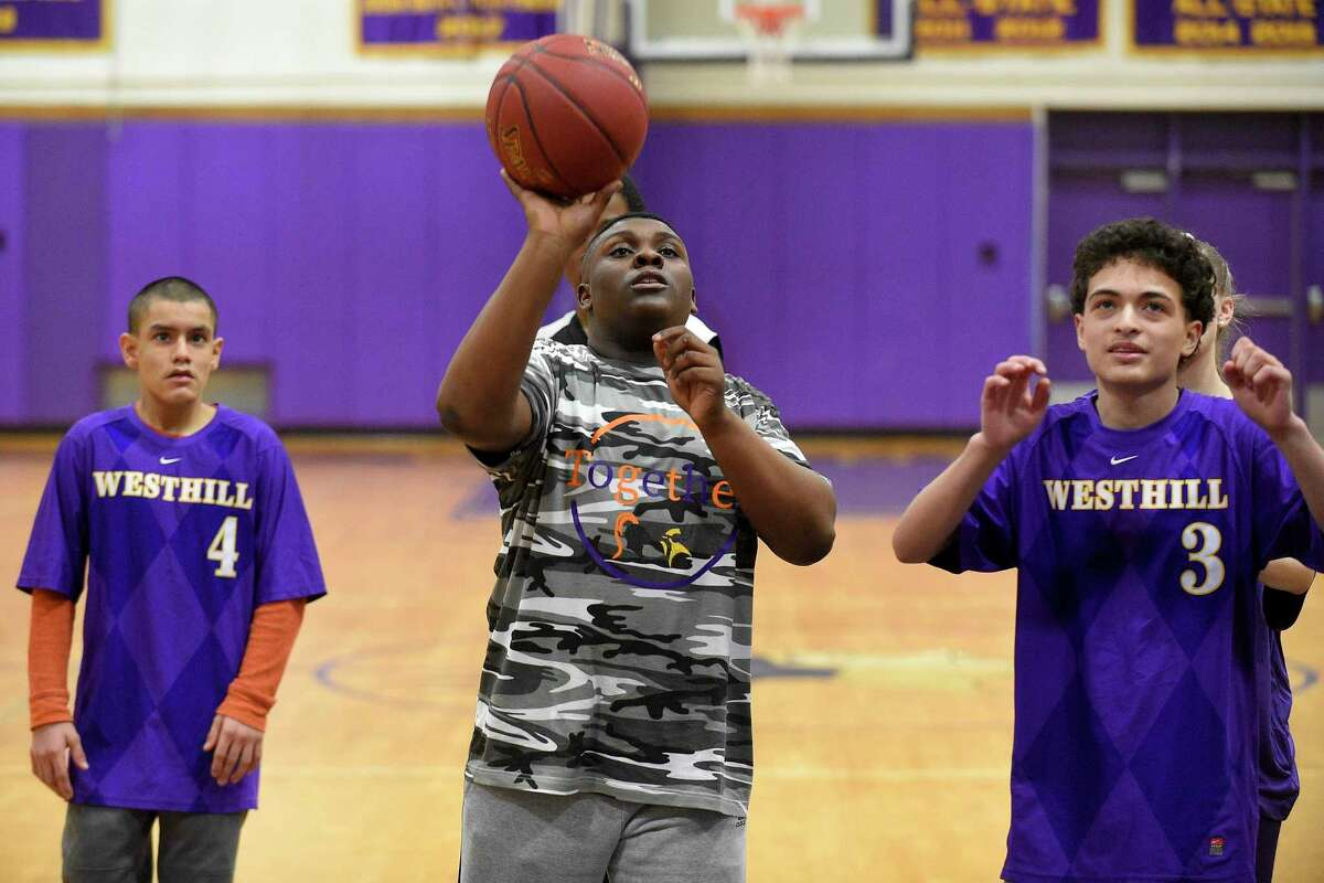 Colin Lawrence puts up a shot as Stamford and Westhill Unified basketball players play to the cheers of fans attending the MLK Basketball Classic at Westhill High School in Stamford, Conn. on Feb. 1, 2020. Players on each team took to the court playing with intensity and heart as they squared up exchanging baskets back and forth. With handlers helping each of the players, shouting encouragement as they shot baskets, each participant consider a winner in every aspect of the game.