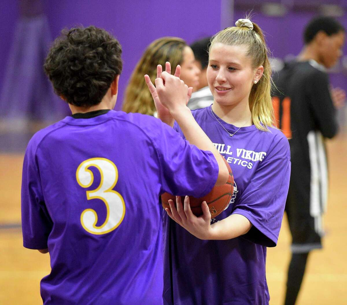 Westhill senior Malina Lasicki exchanges high fives with a participant as Stamford and Westhill Unified basketball players play to the cheers of fans attending the MLK Basketball Classic at Westhill High School in Stamford, Conn. on Feb. 1, 2020. Players on each team took to the court playing with intensity and heart as they squared up exchanging baskets back and forth. With handlers helping each of the players, shouting encouragement as they shot baskets, each participant consider a winner in every aspect of the game.