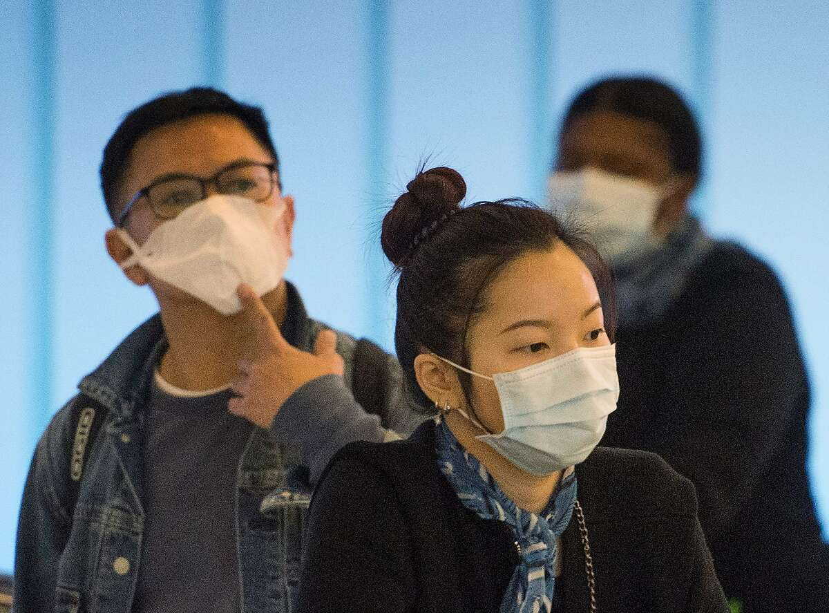 Passengers wear face masks to protect against the spread of the Coronavirus as they arrive on a flight from Asia, at Los Angeles International Airport, California, on February 1, 2020. - A new virus that has killed more than two hundred people, infected thousands and has already reached the US could mutate and spread, China warned, as authorities urged people to steer clear of Wuhan, the city at the heart of the outbreak.