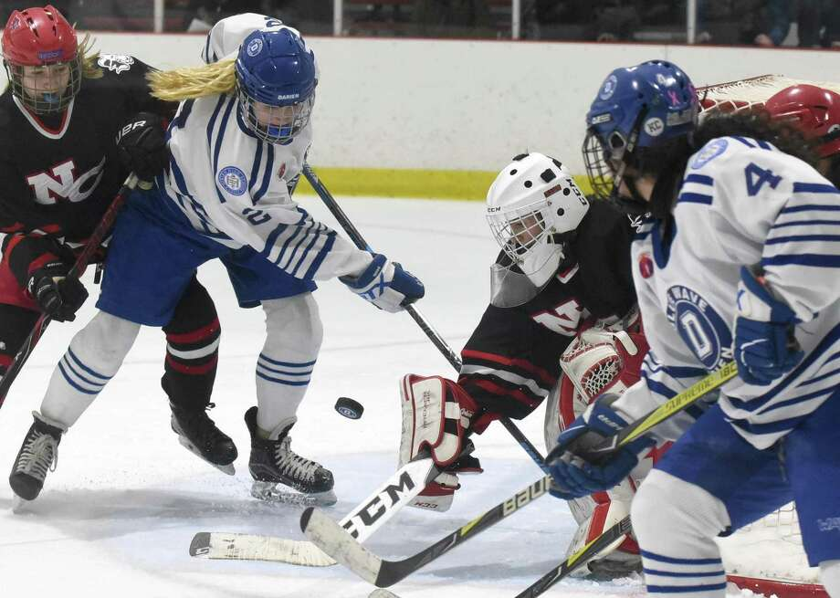 Darien's Colleen Cassidy pressures the net while New Canaan goalie Blythe Novick defends during a game at the Darien Ice House earlier this month. Photo: Dave Stewart / Hearst Connecticut Media / Hearst Connecticut Media