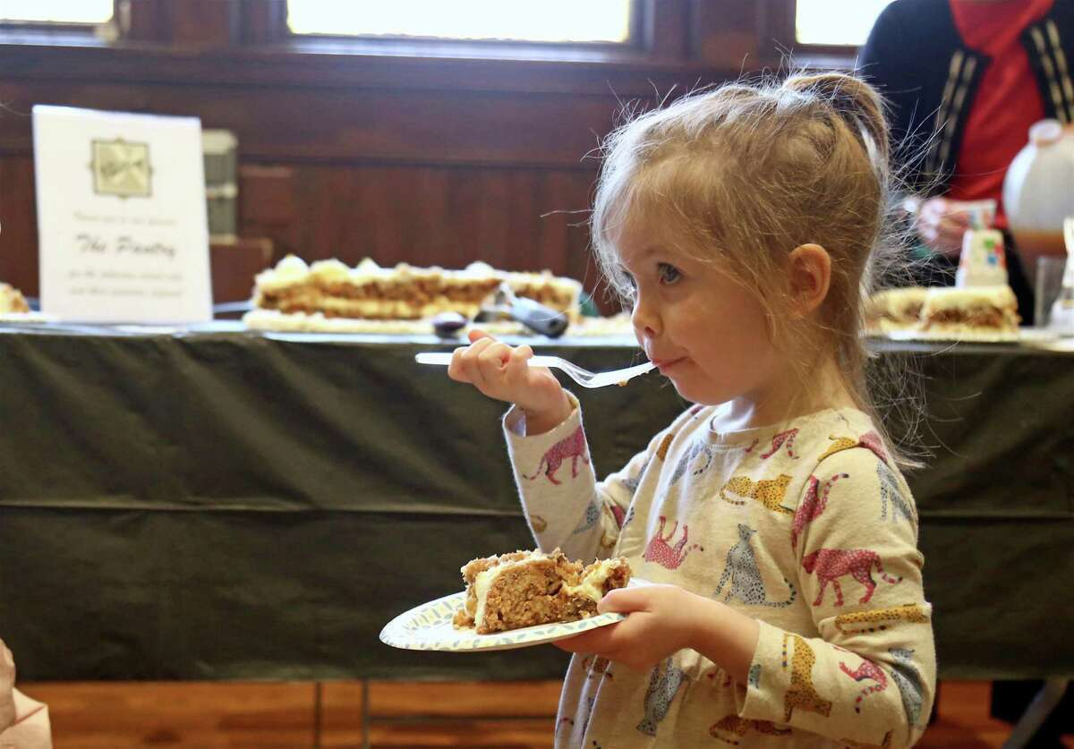 Eloise Fogerty, 2, of Fairfield enjoys some of the carrot cake donated by The Pantry at the Pequot Library's first-ever Edible Book Festival on Saturday, Feb. 1, 2020, in Fairfield, Conn.