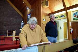Sue Sulzman, left, and Rev. Dan Jones, right, recall the history of the stained glass windows at St Michael's Episcopal Church on Tuesday, Jan. 21, 2020, in Colonie, N.Y. The windows were made by the congregation. (Will Waldron/Times Union)