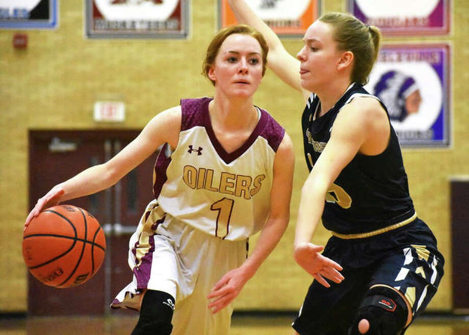 EA-WR's LeighAnne Nottke (left) drives on Father McGivney's Mariah Starnes in the title game at the Dupo Tourney on Nov. 23. The Oilers picked up their 17th win — the most in an EA-WR season since 2005 — on Saturday. Photo: Matt Kamp / Hearst Midwest