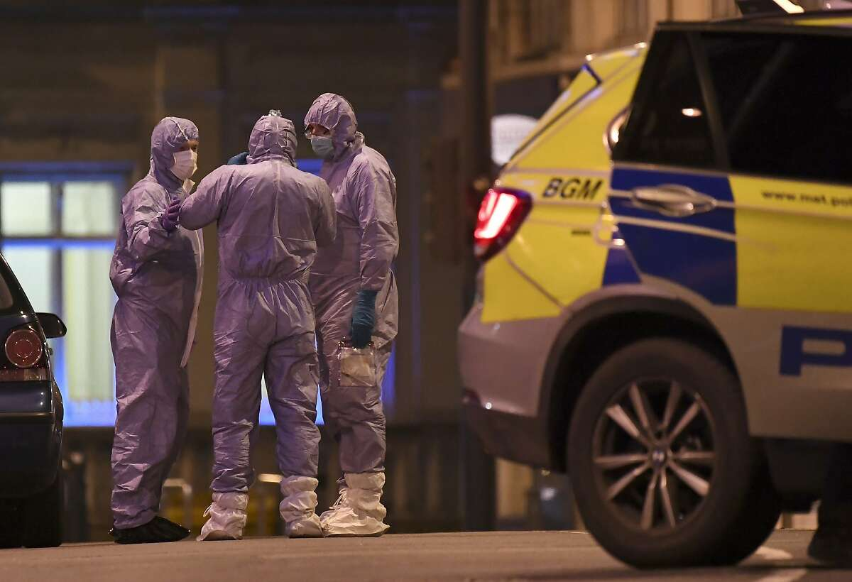 Police forensic officers talk near the scene after a stabbing incident in Streatham London, England, Sunday, Feb. 2, 2020. London police officers shot and killed a suspect after at least two people were stabbed Sunday in what authorities are investigating as a terror attack. (AP Photo/Alberto Pezzali)